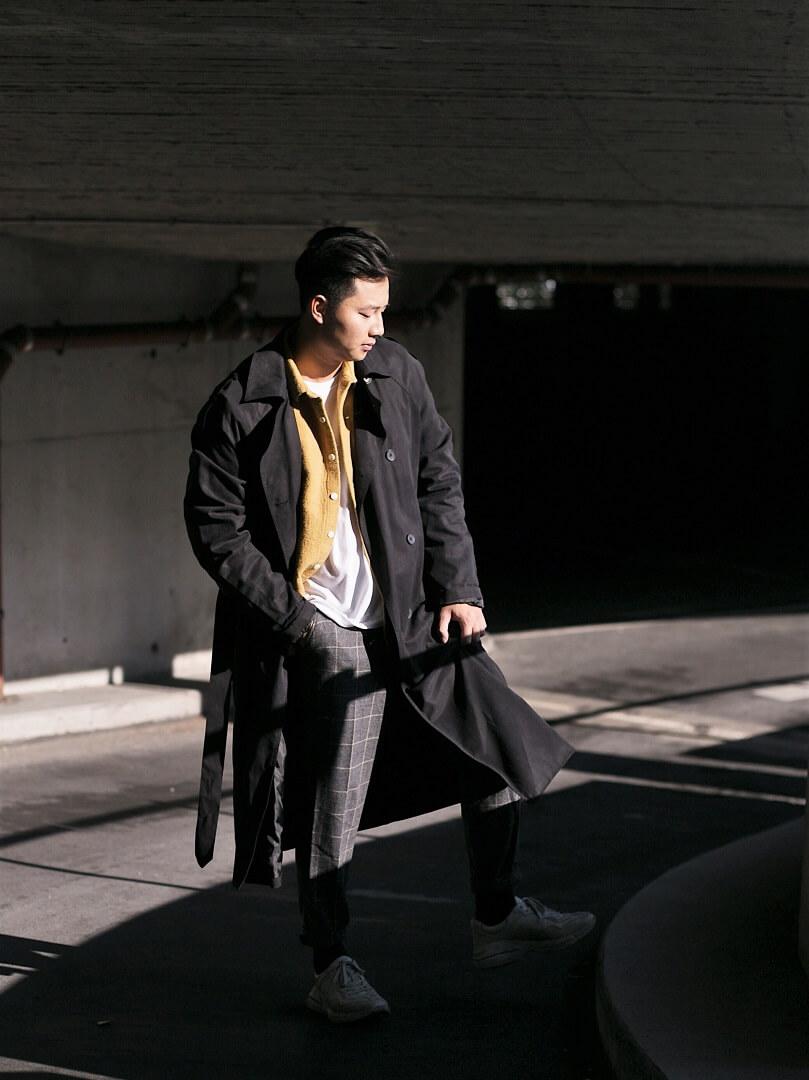 schwarzer langer Trenchcoat mit Gürtel getragen von Duc