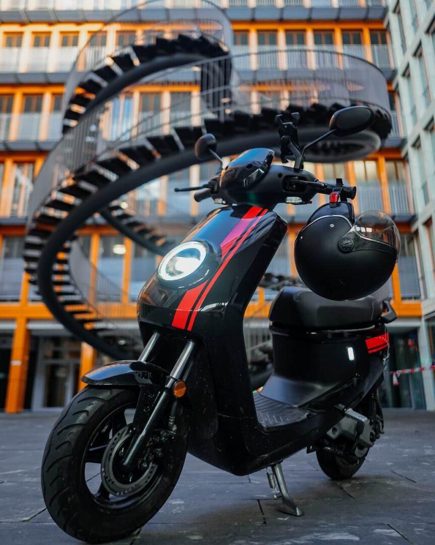 Der NIU MQi+ Sport Elektroroller in schwarz mit roten Rennstreifen